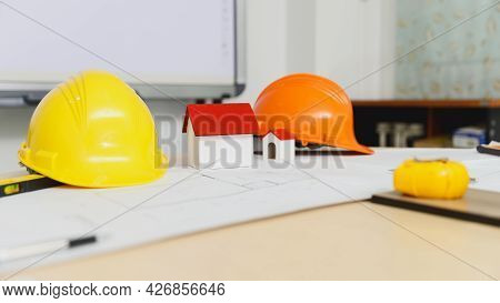 Close Up Image Of A Model House With Helmet On The Desk.