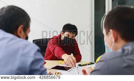 Confident Team Of Architect And Engineer Wearing Protective Masks Working Together In A Office. Arch