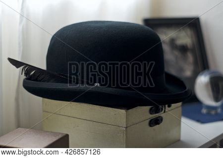 A Man's Black Felt Bowler Hat With Feather Sits On Top Of Wooden Box In Front Of Window.