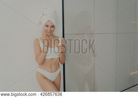 Smiling Young Woman In Towel Wrapped On Head After Shower Using Recommended Moisturizing Facial Crea