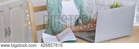 Woman Sitting At A Table Working At A Laptop Computer. Concept Of Remote Work From Home. Home Office