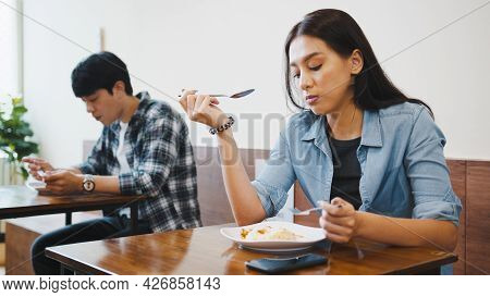 Young Asian Man And Woman Having Lunch Meal In Local Restaurant, Sit In Social Distance. Business Re