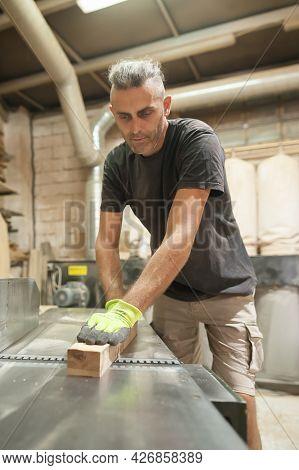Carpenter Processes Wood In A Furniture Workshop