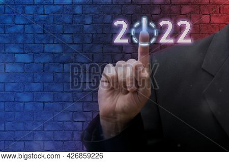 Businessman Pointing Digital 2022 Icon On Neon Blurred Background. Loading Start Happy New Year Conc