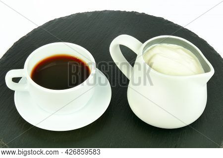 Coffee In A Porcelain Cup And Milk Cream In A Jug Isolated On A White Background.