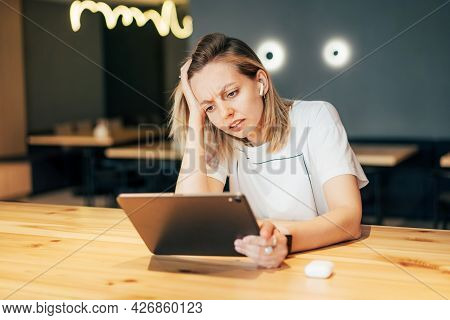 Upset Stressful Woman Looks At The Screen Of A Digital Tablet. Disappointment At Work, Bad News, Mis