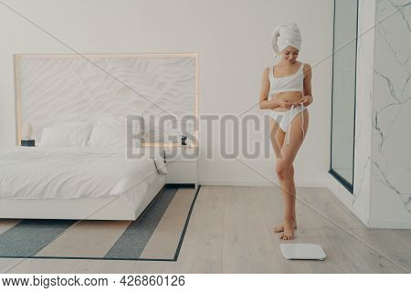 Beautiful Slim Fit Female Model Posing In White Underwear With Measuring Tape In Hand Next To Electr