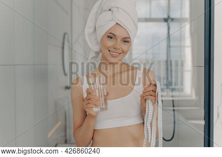 Smiling Attractive Young Caucasian Woman With Glass Of Water In One Hand And Tape Measure In Other,