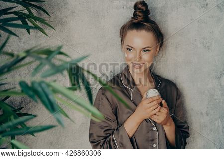 Image Of Caucasian Cheerful Woman In Silk Brown Pajama Smiling While Applying Face Cream Isolated Ov
