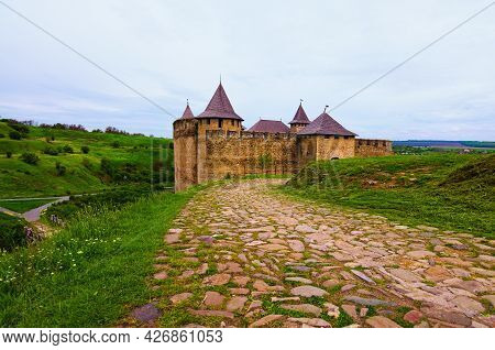 Wide Angle Landscape View Of Ancient Khotyn Castle With Old Cobblestone Road Against Blue Sky. Pictu