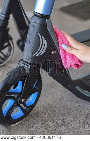 Cleaning Or Washing The Scooter. Electric Scooter Care. A Woman Wipes A Scooter With A Rag After Was