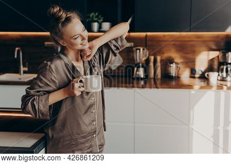 Young Pretty Relaxed Woman In Comfy Pajama Stretching From Sleep Early In Morning While Holding Cup