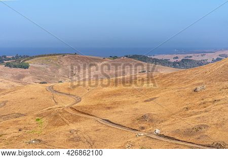 Cambria, Ca, Usa - June 8, 2021: Landscape With Drit Road Through Brown Dry Ranching Land On Hills.