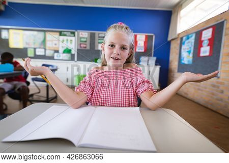 Portrait of caucasian girl sitting on her desk in the class at elementary school. school and education concept