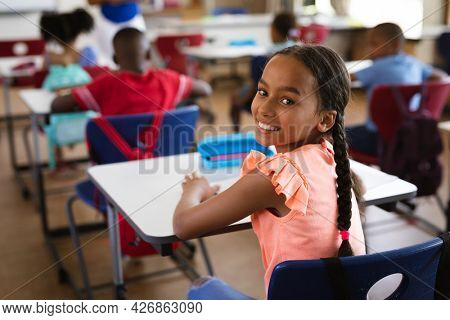 Portrait of african american girl smiling while sitting in the class at elementary school. school and education concept