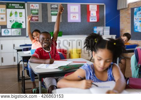 African american boy and girl raising their hands while sitting in the class at elementary school. school and education concept