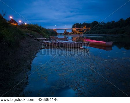 Moored Boats On Sava River In Brod And Bridge In Back On Overcast Summer Evening During Blue Hour