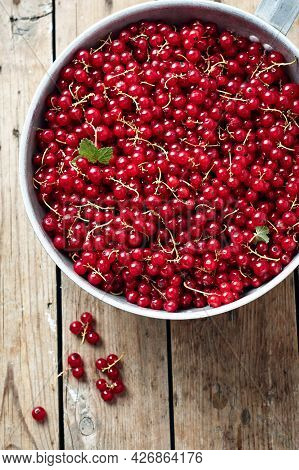 Red Currants In A Bowl On A Wooden Table, Top View.