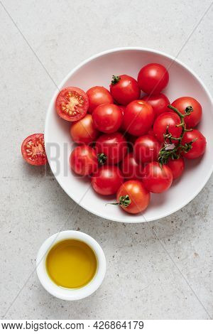 A Bowl Of Fresh Cherry Tomatoes And Olive Oil On A Light Surface.