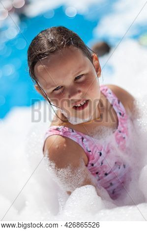 Close-up Portrait Of A Five-year-old Girl In Foam At A Foam Party On A Hot Summer Day On The Beach