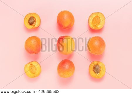Apricots And Sliced Ones At The Pastel Pink Background Top View, Delicious Fresh Summer Apricots
