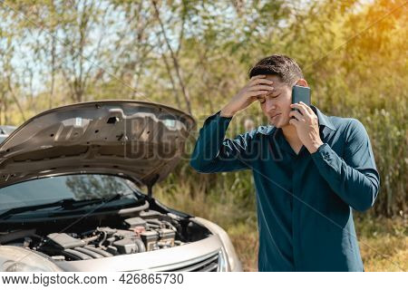 Stressed Man Using Phone For Contact Maintenance Car Service. Car Broken Concept.