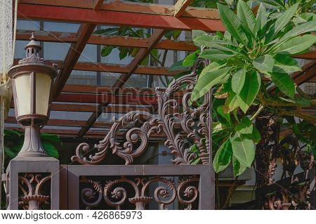 Fragment Of Vintage Handicraft Ornate Forged Front Group With Wrought Elegant Lattice Gate And Lante