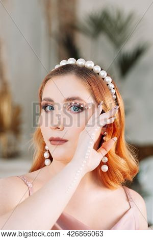 Fashion Portrait Of A Woman With An Orange Curly Square And With Makeup Made Of Mother-of-pearl Bead