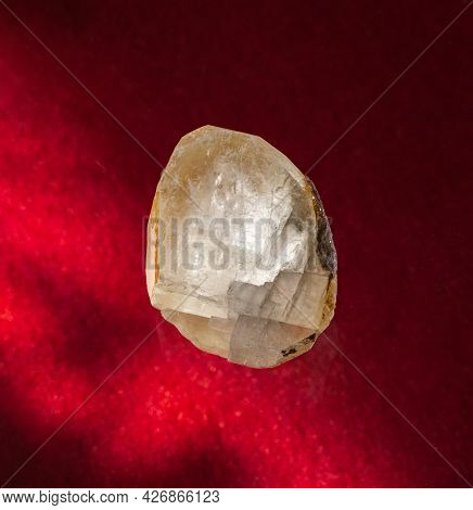 Transparent Calcite Mineral Crystal From Ural, Russia. A Backlight Photo Of A Stone On Red Backgroun