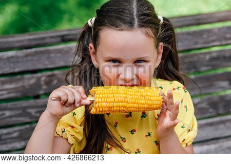 A Charming Six-year-old Girl With Pigtails In A Yellow Dress Has A Delicious Cob Of Corn On A Walk F