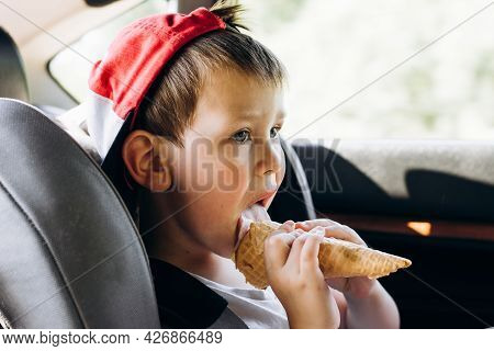 Portrait Of A Cute Kid In A Red Cap Eating Ice Cream In A Waffle Cone While Traveling In A Child's C
