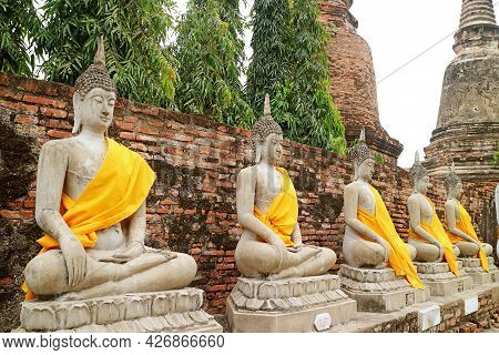 Row Of The Amazing Buddha Images In Yellow Robes With Group Of Stupas In Backdrop, Wat Yai Chai Mong