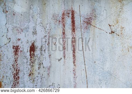 The Surface Of An Old Metal Wall. There Are Several Partially Destroyed Layers Of Paint Of Different