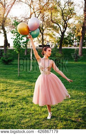 Lifestyle Portrait Of Elegant Ballerina In A Pink Silk Dress And White Pointe Shoes Balancing On Tip