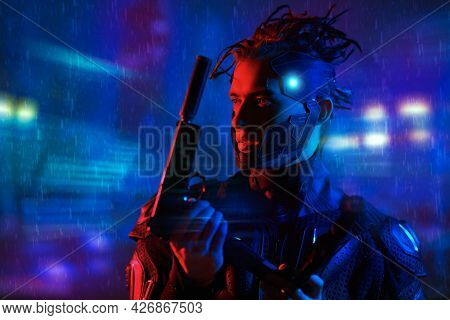 Game, virtual reality. A courageous cyber warrior fights with gun in his hands against the backdrop of the night city of the future. Cyber concept.