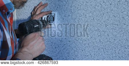 A Man Fixes The Base Of The Switch In The Socket In The Wall Using An Electric Screwdriver, Backgrou