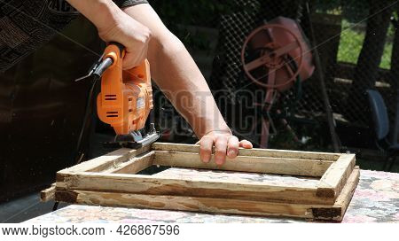 Shaping An Old Shabby Wood Frame With An Electric Jigsaw Outdoors, Men's Woodworking Outdoors, Renew