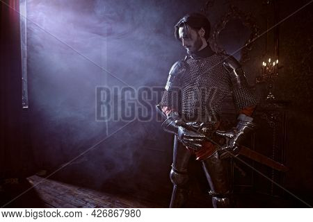 The noble knight in armor knelt down with his sword and looks at the light in the castle. Romance.