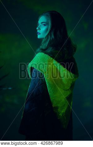 Portrait of beautiful model girl in a stylish coat poses in yellow and green light in dark at the studio. Fashion collection. Haute couture clothing.