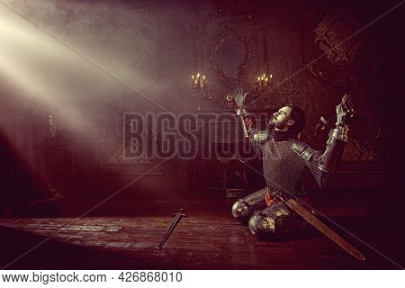 Emotional heartbroken noble knight in armor knelt down and raised two hands, looking at the light in the castle.