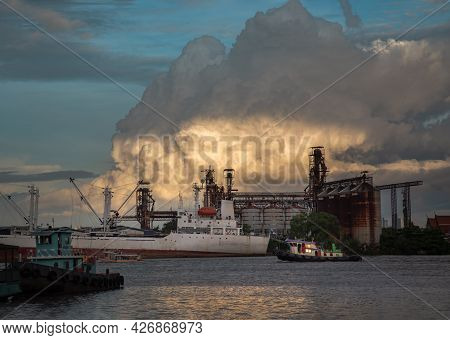A Cargo Ship Parked In Front Of Petroleum Refinery On The Chao Phraya River In The Evening. Selectiv
