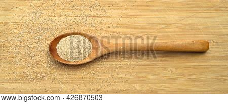 Active Granulated Yeast, Instant Dry Sourdough, On A Bamboo Cutting Board In Wooden Spoon