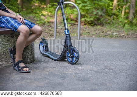 Walk In The Park On A Scooter. A Young Guy Sits On A Bench And Rests While Walking On A Smokat. Ecol