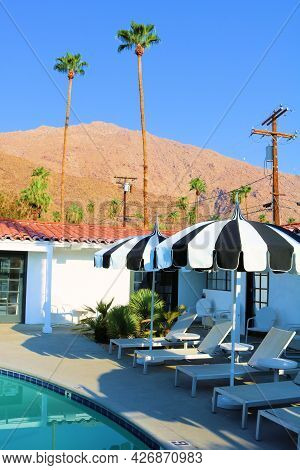 July 14, 2021 In Palm Springs, Ca:  Poolside Seating With Umbreelas Besides A Pool Taken On A Courty