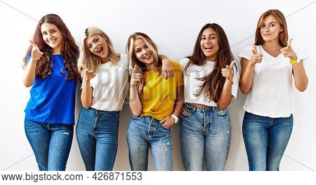 Group of young girl friends standing together over isolated background pointing fingers to camera with happy and funny face. good energy and vibes.