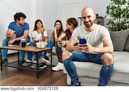 Group of young friends having party sitting on the sofa at home. Man smiling happy using smartphone at home.