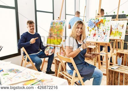 Group of middle age artist at art studio pointing aside worried and nervous with forefinger, concerned and surprised expression