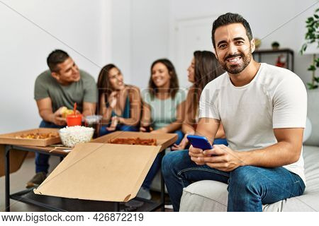 Group of young hispanic friends eating italian pizza sitting on the sofa. Man smiling happy and using smartphone at home.