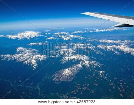 View Of A Snowcapped Mountain Landscape From An Airplane