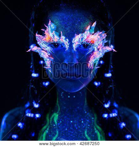 Portrait of beautiful woman with body art glowing in ultraviolet light
